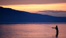 Pesca en la puesta del sol fotografía de archivo libre de regalías