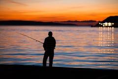 Pesca en la puesta del sol fotos de archivo libres de regalías