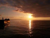 Pesca en mar en la puesta del sol foto de archivo