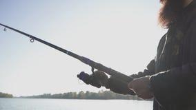 Pesca farpada do pescador com uma vara de pesca no rio Pesca do rio Movimento lento filme