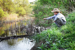 Pesca felice del ragazzo sul fiume Immagine Stock