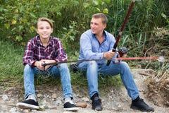 Pesca feliz del hombre y del muchacho en el río de agua dulce Imagenes de archivo