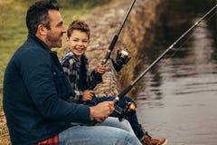 Pesca feliz del hombre y del niño en un lago foto de archivo