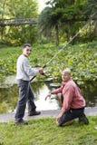 Pesca hispánica del adolescente y del padre en la charca Imagen de archivo libre de regalías
