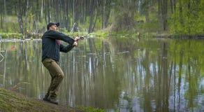 pesca Il pescatore nell'azione, uomo sta facendo una colata Fotografie Stock