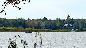 Pesca inidentificable de los pares en un barco en un lago almacen de video