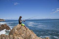 Pesca joven del adolescente por el mar Imágenes de archivo libres de regalías