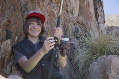Pesca joven del adolescente por el mar Foto de archivo libre de regalías