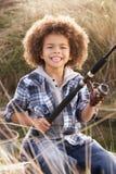 Pesca joven del muchacho en la playa Fotografía de archivo