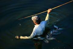 Pesca local con una lanza, Amarapura, Myanmar del hombre Fotos de archivo