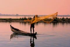 Pesca locale dell'uomo con una rete al tramonto, Amarapura, Myanmar immagine stock