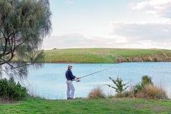 Pesca masculina do aposentado em um rio fotografia de stock
