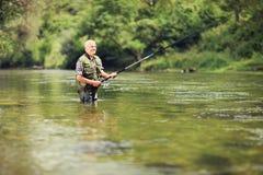 Pesca matura del pescatore in un fiume Immagini Stock