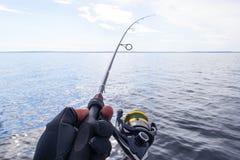Pesca no lago M?os do pescador com vara de pesca Tiro macro A vara de pesca e as m?os do pescador sobre o lago molham girar imagem de stock royalty free