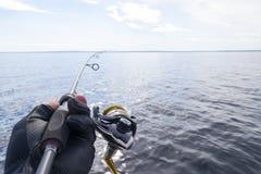 Pesca no lago M?os do pescador com vara de pesca Tiro macro A vara de pesca e as m?os do pescador sobre o lago molham girar imagens de stock royalty free