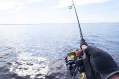 Pesca no lago M?os do pescador com vara de pesca Tiro macro A vara de pesca e as m?os do pescador sobre o lago molham girar foto de stock