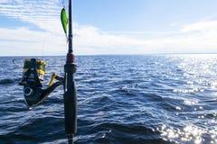 Pesca no lago M?os do pescador com vara de pesca Tiro macro A vara de pesca e as m?os do pescador sobre o lago molham girar fotos de stock royalty free