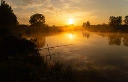 Pesca no lago nevoento no amanhecer imediatamente depois do nascer do sol dourado imagens de stock