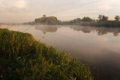 Pesca no lago nevoento no amanhecer imediatamente depois do nascer do sol dourado imagem de stock