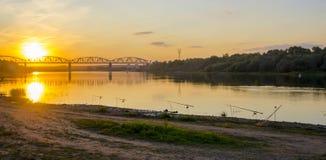 Pesca no por do sol perto da ponte sobre o rio Fotos de Stock Royalty Free