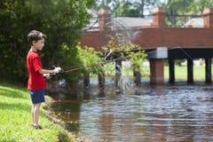 Pesca nova do menino em um rio Foto de Stock Royalty Free