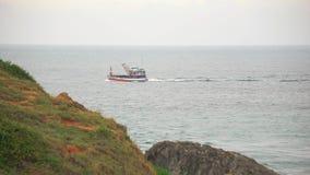 Pesca o barco de carga que flota tranquilamente en las aguas del océano, orilla rocosa en el primero plano almacen de video