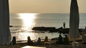 Pesca por el mar en la puesta del sol Foto de archivo libre de regalías