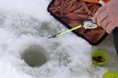 Pesca por una barra plástica del invierno en el agujero del hielo en la charca fotografía de archivo