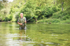 Pesca relaxado do pescador no rio em um dia ensolarado Imagem de Stock