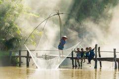 Pesca rural del hombre por la red de pesca mientras que grupo de niños rurales Fotos de archivo libres de regalías