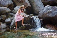 Pesca sorridente della ragazza in una torrente montano Immagine Stock