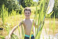 Pesca sveglia del ragazzo con una rete su un lago immagine stock libera da diritti
