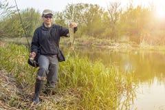 Pesca Trofeo y ca?a de pescar felices de los pescados del lucio de la tenencia del pescador en el r?o foto de archivo