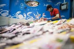 Pescadero que coloca los pescados en la tienda de los pescados imagen de archivo
