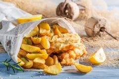 Pescado frito con patatas fritas calientes servidos en papel con el limón foto de archivo libre de regalías