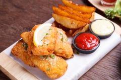 Pescado frito con patatas fritas con la cuña de la patata Fotos de archivo