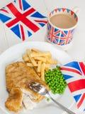 Pescado frito con patatas fritas con una taza de té en una taza y un britis del Union Jack Imágenes de archivo libres de regalías