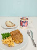 Pescado frito con patatas fritas con una taza de té y pan y mantequilla Fotos de archivo
