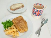 Pescado frito con patatas fritas con una taza de té y pan y mantequilla Imagen de archivo