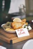 Pescado frito con patatas fritas curruscantes con los guisantes y el limón, comida de la calle Fotos de archivo libres de regalías