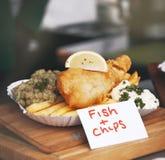 Pescado frito con patatas fritas curruscantes con los guisantes y el limón, comida de la calle, al aire libre Fotografía de archivo libre de regalías
