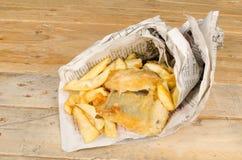 Pescado frito con patatas fritas en periódico Fotos de archivo