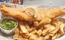 Pescado frito con patatas fritas en periódico Imagen de archivo
