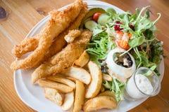 Pescado frito con patatas fritas gastrónomos con la ensalada Imagen de archivo libre de regalías