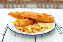 Pescado frito con patatas fritas ingleses tradicionales Imagen de archivo libre de regalías