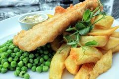 Pescado frito con patatas fritas ingleses tradicionales de la comida con los guisantes verdes Fotografía de archivo libre de regalías