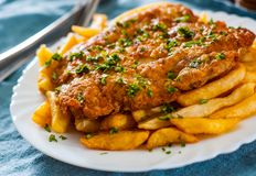 Pescado frito con patatas fritas Prendedero y patatas fritos de pescados en una placa blanca Fotografía de archivo