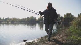 Pescador adulto com caminhadas longas da barba perto do rio com rede das varas de pesca e dos peixes o homem olha na distância filme