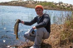 Pescador afortunado feliz que guardara uma carpa grande no rio Foto de Stock Royalty Free