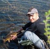 Pescador afortunado feliz que guardara a carpa grande na pesca Fotografia de Stock Royalty Free